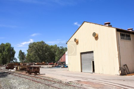 Rusted metal mining wagons standing outside an industrial warehouse with train tracks running in front of the building