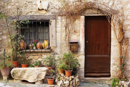 Street garden with Street name and potted plants in front of windows and doors in the quaint little French hilltop village of Saint-Paul de Vence, Southern France, a Heritage Site