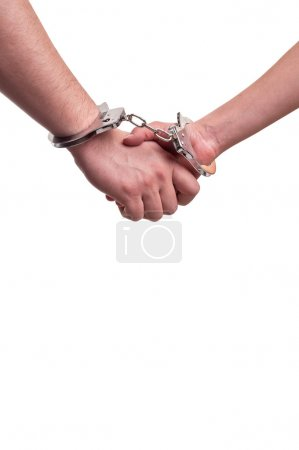 Man and woman holding hands in handcuffs - relationship concept