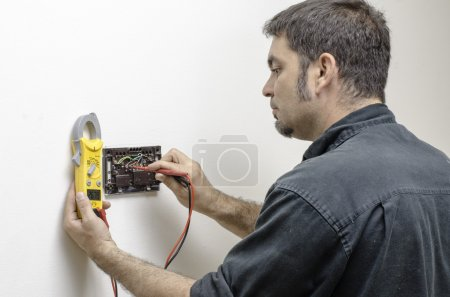 Photo for HVAC technician testing voltage on a mercury thermostat. - Royalty Free Image