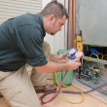 HVAC technician charging a heat pump with refriger...