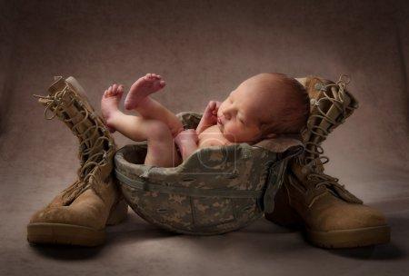 Photo pour Un enfant dans son casque armée de pères avec bottes - image libre de droit