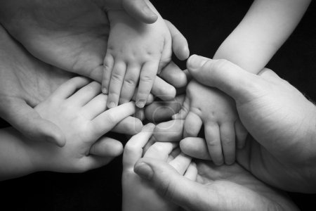 Photo for A young family of four holding hands - Royalty Free Image