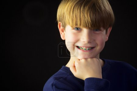 A Young Boy Shows off his Green Braces
