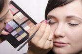 Vizážistka v procesu make-up barvy horní víčka modelu