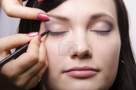 Makeup artist in the process of makeup colors upper eyelids model