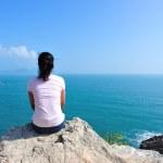 Back of  woman sit on seaside rock, back view...