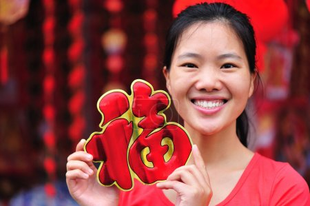 """Young asian woman hold a chinese character """"fu"""""""
