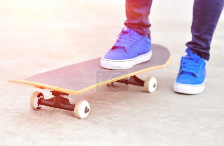 Photo for Legs in sneakers on a skateboard - Royalty Free Image