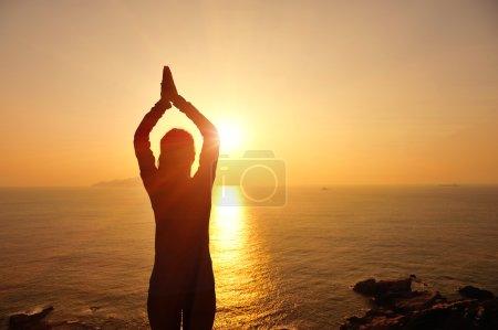 Woman meditation at sunrise seaside