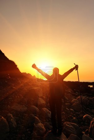 Cheering woman open arms to the sunrise