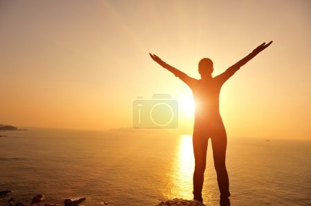 Woman opening arms under sunrise