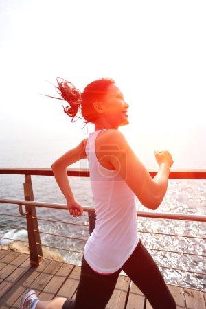 Photo pour Heureuse femme asiatique en cours d'exécution au bord de mer de lever du soleil. mode de vie sain - image libre de droit