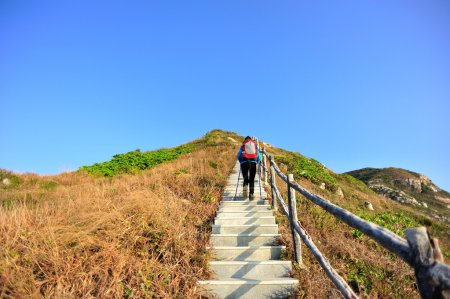 Photo for Hiking woman climbing the stone stairs to mountain peak - Royalty Free Image
