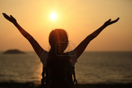 Photo for Cheering woman open arms at sunset seaside beach - Royalty Free Image