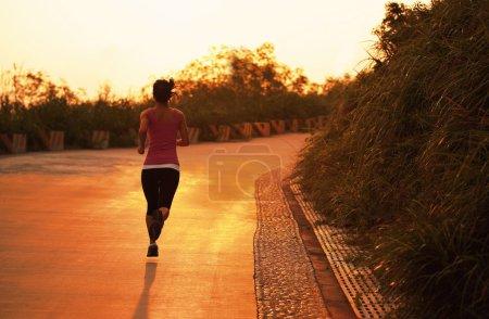 Woman running at seaside under sunrise