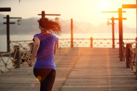 woman running on wooden pier