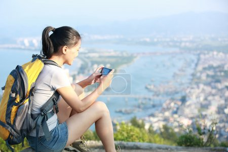 Young woman hiker use smart phone