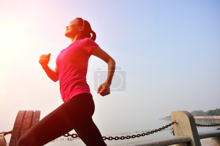 Woman running at seaside under morning sunrise