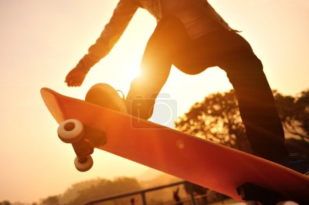 Photo for Skateboarding woman on sunrise - Royalty Free Image