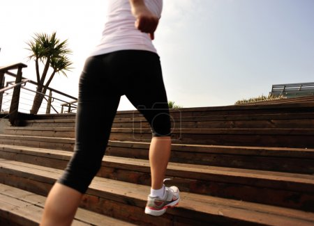Runner athlete running on seaside stone stairs