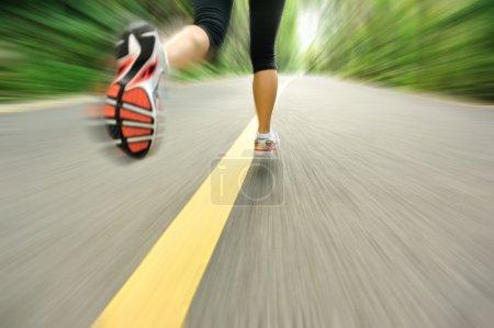 Woman runner athlete legs running on road