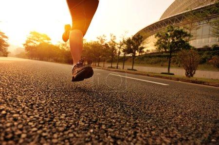 Runner athlete running on tropical park trail