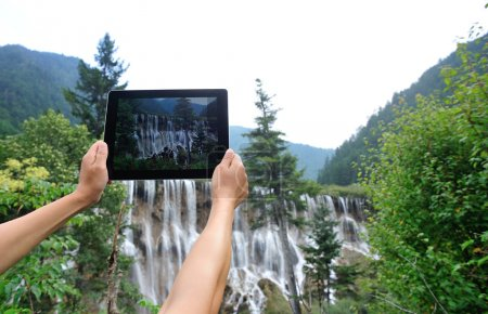 Woman tourist hand taking photo with digital tablet