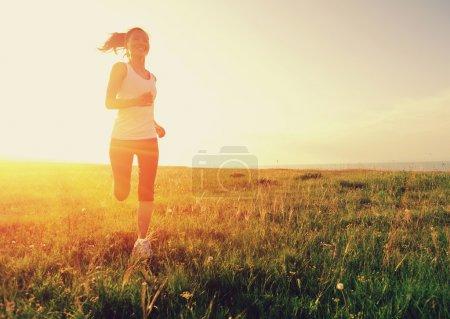Runner athlete running on grass seaside.