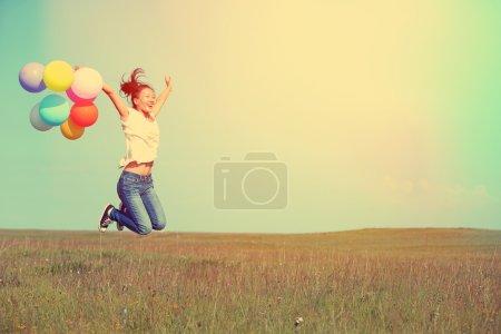 Photo pour Jeune femme asiatique courir et sauter sur la prairie verte avec des ballons colorés - image libre de droit