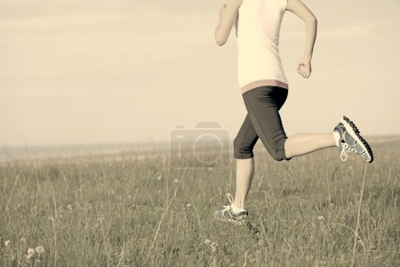 Photo for Runner athlete running on grass seaside. woman fitness  jogging workout wellness concept. - Royalty Free Image