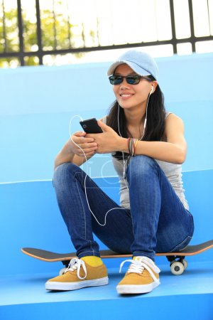 Woman skateboarder listening music