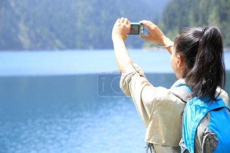 Photo pour Femme touriste, photographe prenant des photos avec appareil photo numérique dans le parc national de jiuzhaigou, Chine - image libre de droit