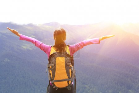 Cheering hiking woman open arms