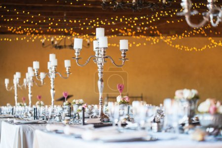 Wedding reception hall with decor including candles and cutlery
