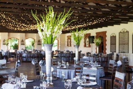 Photo pour Lieu de réception avec tables décorées et guirlande lumineuse en arrière-plan, mise au point sélective de mariage - image libre de droit