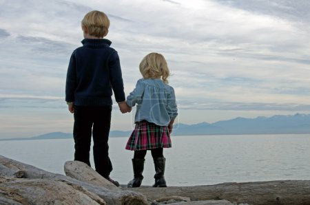Young brother and sister holding hands looking out at sea