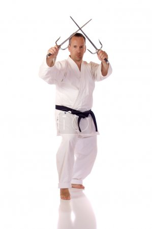 Photo for Man in karate-gi holding a pair of sai - Royalty Free Image