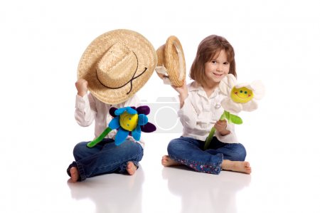 Photo for Cute little brother and sister playing with hats and flowers - Royalty Free Image