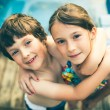 Brother and sister hugging in bathing suit in fron...