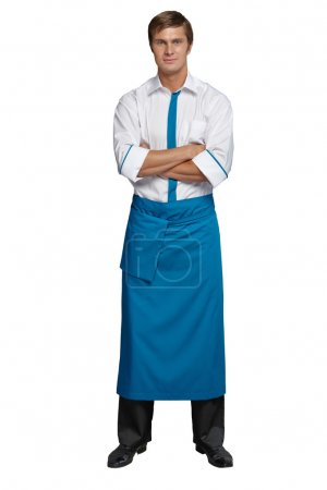Photo for Young man in the form of a waiter or chef, white and red shirt, blue and black apron, black pants - Royalty Free Image