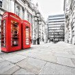 Two red phone booths on the street...