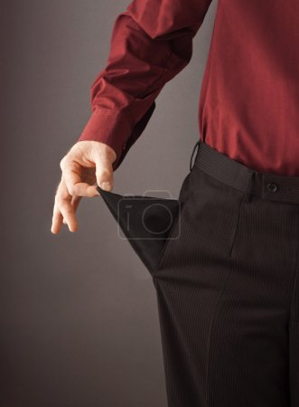 Poor businessman turning his empty pocket inside out to show his broke and out of money.