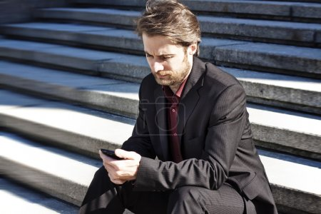 Forty years old businessman seating on stairs outside office building looking on a mobile phone