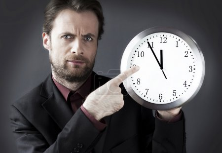 Forty years old strict demanding boss with a pointing finger on a clock - indicates a deadline hour