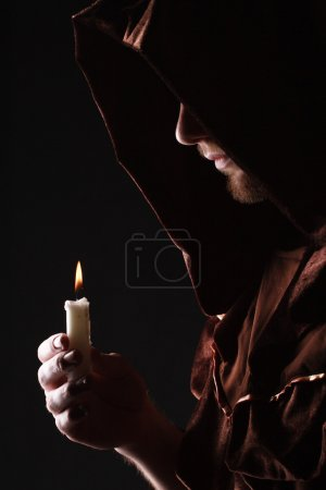 wizard in black cape with candle