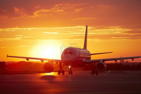 Photo for Airplane at sunset - back lit - Royalty Free Image