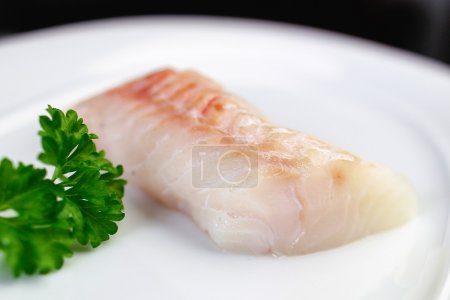 Photo for Close-up of four uncooked herring fishs lying on white plate - Royalty Free Image