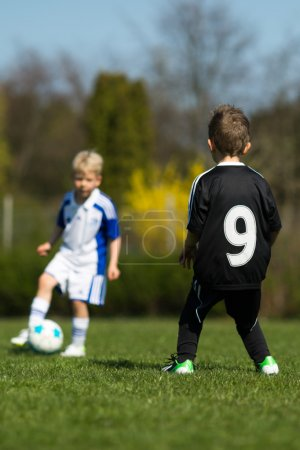 Two kids playing soccer
