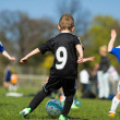 Boys playing soccer outside during summer time. Tr...